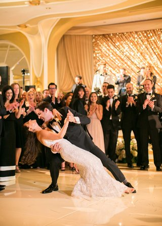 wedding-guests-clap-as-groom-dips-bride-during-first-dance-in-monique-lhuillier-wedding-dress