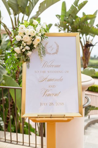 wedding-welcome-sign-in-gold-frame-with-flower-arrangement-in-the-corner