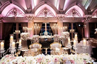 wedding-reception-with-mirror-sweetheart-table-tufted-armchairs-candelabra-violet-lighting
