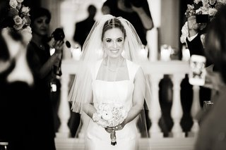 black-and-white-photo-of-bride-walking-down-aisle-with-veil