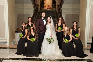 bride-with-groom-in-burgundy-suit-with-bridesmaids-in-black-cap-sleeve-dresses-green-bouquets