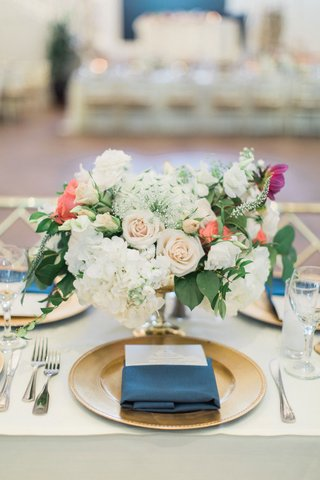 wedding-reception-table-gold-charger-plate-navy-blue-napkin-menu-low-flower-arrangement-hydrangea