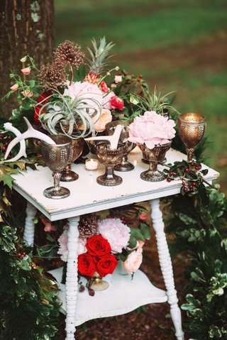 outdoor-wedding-reception-table-with-red-roses-pink-peonies-airplants-antlers-in-goblets
