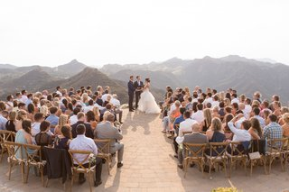 beautiful-views-mountain-canyon-malibu-wedding-ideas-helipad-stone-brick-wood-chairs-guests-watching