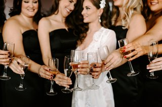 bride-in-white-robe-dressing-gown-headpiece-black-bridesmaid-dresses-champagne-cheers-getting-ready