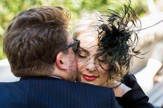 groom-in-blue-pinstripe-suit-kisses-blonde-bride-in-black-dress-feather-headpiece-red-lipstick