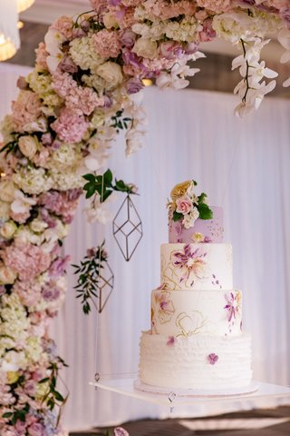 wedding-cake-with-lavender-top-tier-ruffle-bottom-layer-and-middle-layers-of-floral-hand-painted