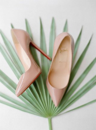 wedding-shoes-nude-tan-christian-louboutin-heels-with-red-soles-on-green-palm-frond