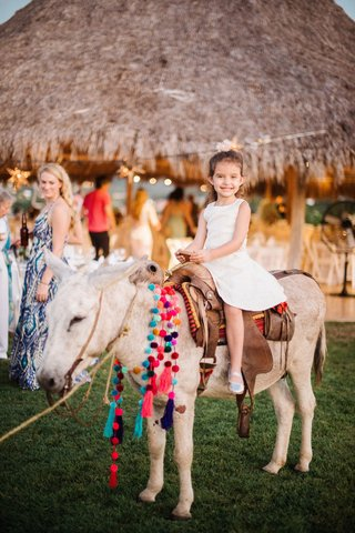 mexico-wedding-welcome-party-little-girl-on-donkey-with-saddle-and-necklace-pom-poms-on