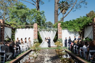 wedding-ceremony-belmond-el-encanto-lily-pond-aisle-with-lily-pads-on-both-sides-and-guest-chairs