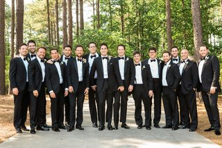 groom-and-groomsmen-in-tuxedo-suits-with-bow-ties-in-wooded-area-georgia-wedding