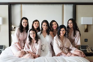 bride-in-lace-trim-white-robe-getting-ready-photo-with-bridesmaids-and-flower-girls