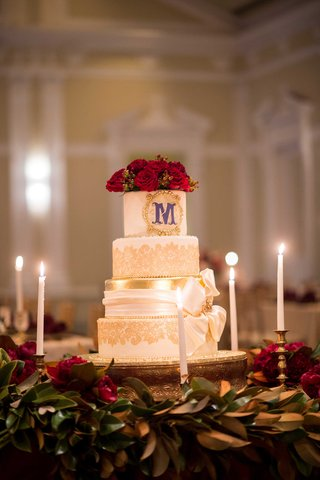 white-cake-red-flowers-purple-monogram-initial-gold-details-candles-ribbon-renaissance-wedding