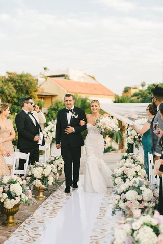 bride-in-mermaid-wedding-dress-walking-down-white-aisle-gold-scroll-motif-white-pink-flowers-father