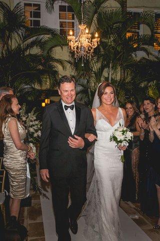 bride-in-randi-rahm-wedding-dress-walks-down-outdoor-aisle-night-chandelier-palm-trees