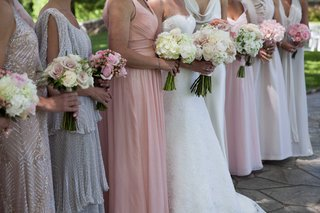 a-bride-stands-with-her-bridesmaids-in-varying-styles-and-colors-of-dresses-with-different-bouquets