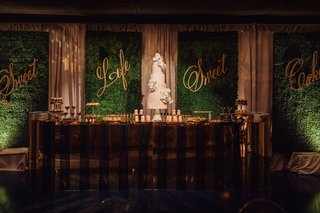 wedding-cake-and-desserts-on-table-in-front-of-hedge-wall-with-gold-calligraphy-signs-sweet-life