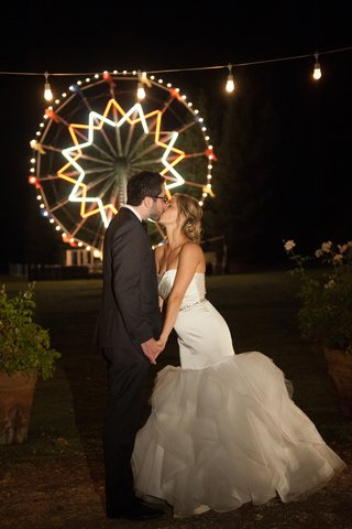 bride-and-groom-kissing-in-front-of-carnival-ride