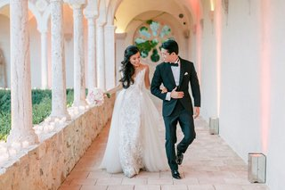 bride-in-illusion-wedding-dress-with-overskirt-long-hair-pulled-to-side-with-groom-terrace-pathway