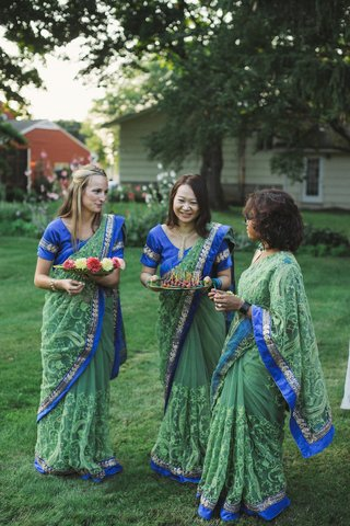 women-in-blue-and-green-saris-passing-food-to-guests