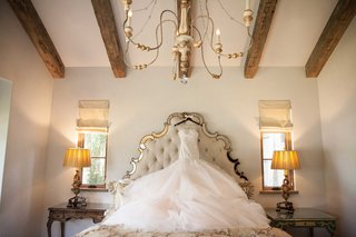 monique-lhuillier-wedding-dress-hanging-up-on-ornate-headboard-in-rustic-bridal-suite-with-wood-beam