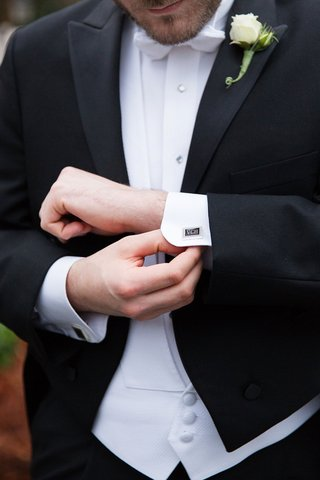 groom-adjusting-cuff-links-with-monogram-cufflink-cufflinks-white-vest-and-bow-tie-rose-boutonniere