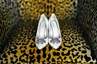 leopard-print-chair-displaying-white-wedding-shoe-pumps-with-brooches-on-toes