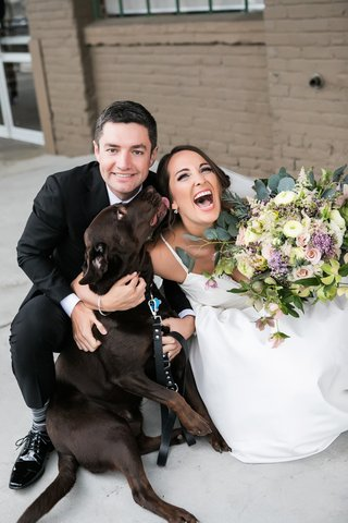 groom-grins-with-laughing-bride-dog-licks-brides-face