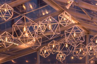 clear-topped-tent-geometric-light-fixtures-with-round-edison-filament-light-bulbs