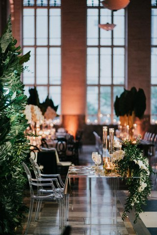 wedding-reception-sweetheart-table-acrylic-lucite-ghost-chairs-greenery-white-orchid-tall-candles