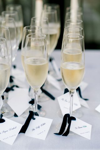 wedding-reception-champagne-in-flute-glasses-blue-velvet-ribbon-with-square-escort-card-table-number