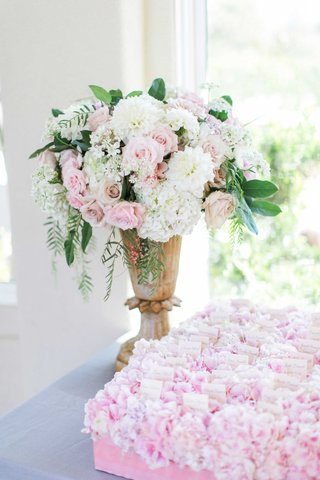 urn-filled-with-white-hydrangea-pink-rose-and-green-leaves-at-escort-card-table-with-pink-flowers