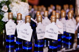mini-blue-wine-bottles-and-gold-wax-with-seating-card-tags-at-wedding