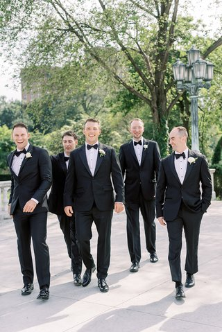 wedding-portrait-of-groom-and-groomsmen-in-tuxedos-walking-at-venue-cleveland-museum-of-art-outdoor