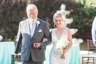 bride-in-a-sleeveless-claire-pettibone-dress-is-escorted-by-father-of-bride-in-grey-suit