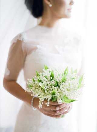 bride-in-vera-wang-wedding-dress-holding-small-bouquet-of-lily-of-the-valley-blooms-flowers