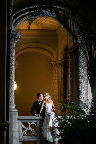 wedding-portrait-photography-couple-photo-bride-sitting-on-railing-groom-kisses-from-behind-her