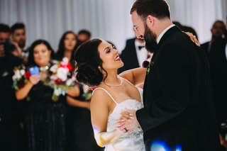 wedding-reception-first-dance-bride-with-necklace-and-spaghetti-strap-dress-for-easy-dancing-updo