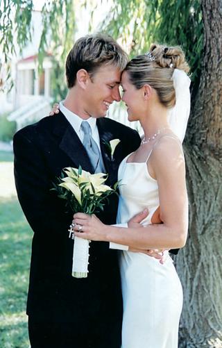 bride-in-sleek-dress-hugs-groom-while-holding-bouquet