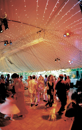 guests-dance-at-tented-reception-with-string-lights