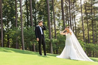 bride-covering-her-eyes-on-grass-lawn-before-first-look-with-groom-in-forest-groom-covering-eyes-too