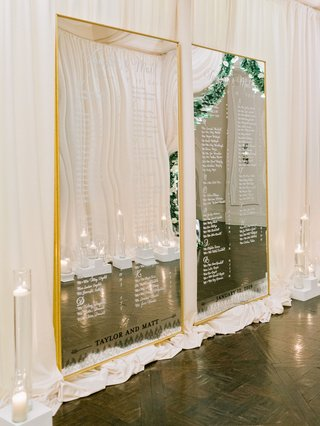 wedding-reception-entrance-seating-chart-mirror-gold-frame-white-script-candles-hallway