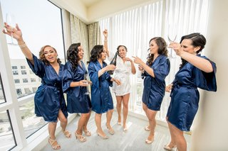 bride-in-white-bridal-robe-bridesmaids-in-navy-robes-celebrate-with-champagne-while-getting-ready