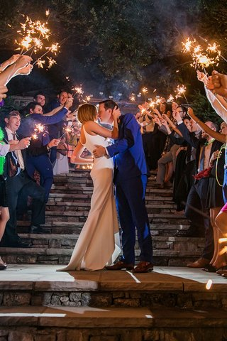 bride-in-wedding-dress-groom-in-blue-suit-guests-holding-sparklers-on-staircase-stone
