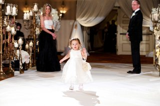 flower-girl-in-white-dress-tights-and-shoes-walking-down-aisle-with-flower-pomander-on-wrist
