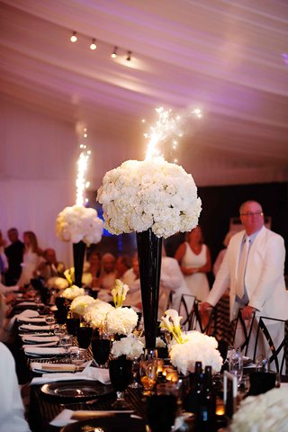 white-tall-flower-arrangement-with-sparklers-coming-out-of-centerpiece