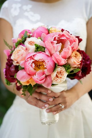 bride-holding-bouquet-of-hot-pink-peony-garden-rose-and-red-burgundy-blooms
