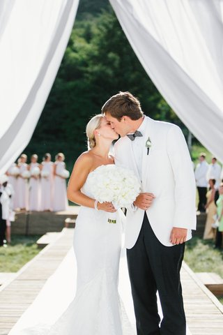 bride-in-white-wedding-dress-and-bouquet-kissing-groom-after-getting-married-outdoors-white-tuxedo