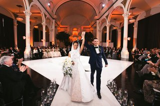 bride-and-groom-announced-husband-and-wife-ceremony-seating-in-the-round-vibiana-columns-white-stage