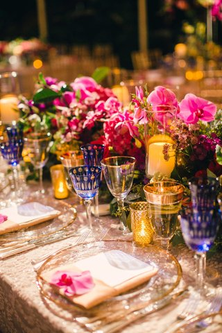 orchid-bloom-at-wedding-place-setting-with-pink-low-flower-table-runner-centerpiece
